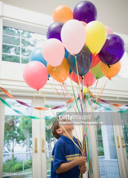 Boy holding bunch of balloons indoors