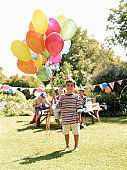 Boy (5-7) holding bunch of balloons outdoors, friends in background