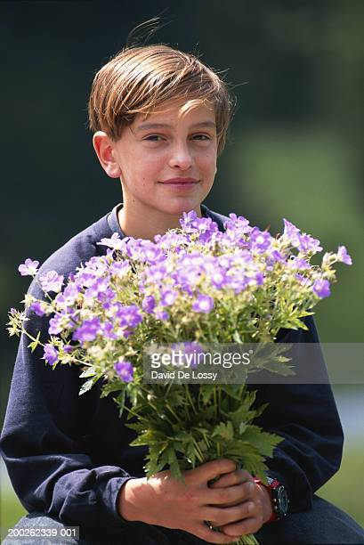 Boy (10-13) holding bunch of flowers
