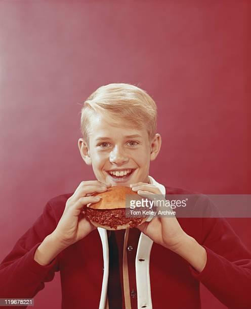 Boy holding burger, smiling, portrait