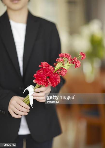 Boy holding carnation flowers