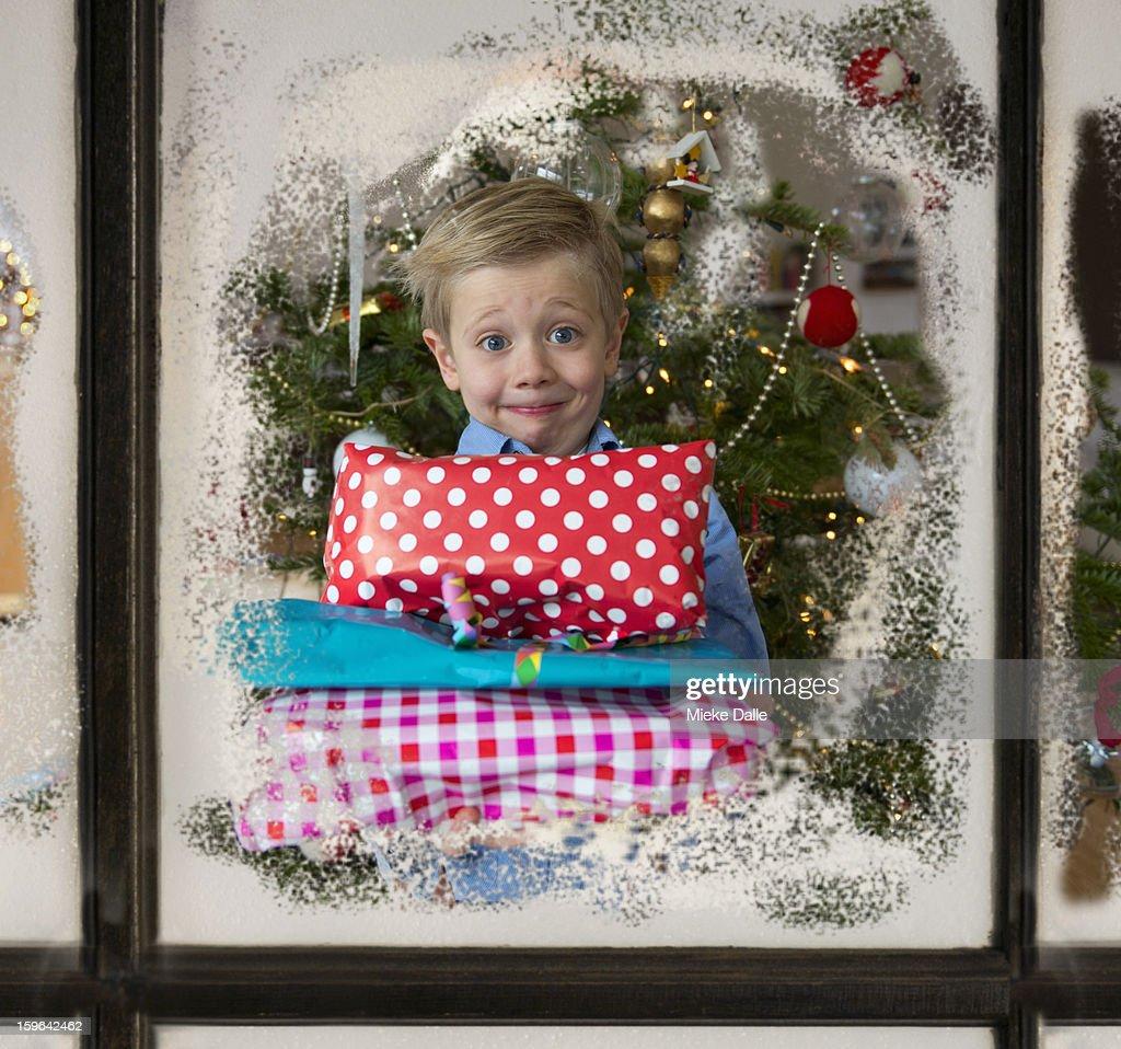 A boy holding Christmas presents : Stock Photo