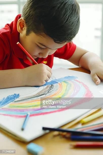 Boy holding colour pencil, drawing a rainbow