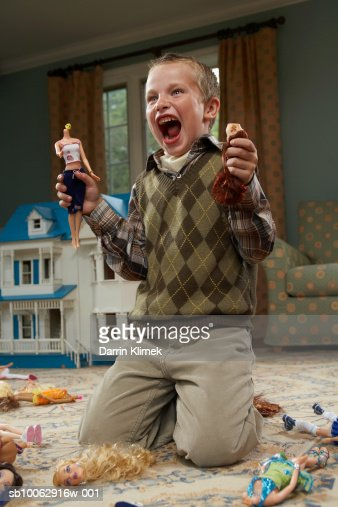 Boy (6-7 years) holding decapitated dolls and yelling