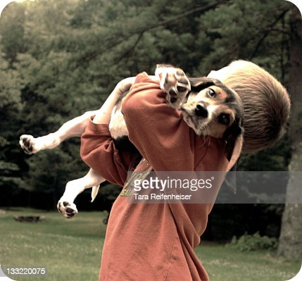 boy holding dog in arms : Stock Photo