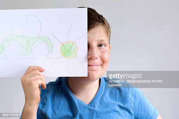 Boy holding drawing of car and sun