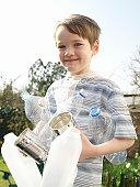 Boy (5-7) holding empty bottles in garden, smiling