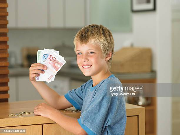 Boy (7-9) holding euro notes, smiling, portrait