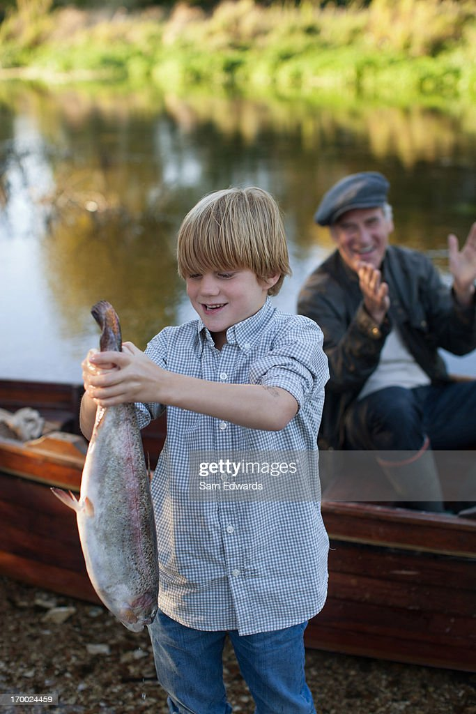 Boy holding fish in front of lake : Stock Photo