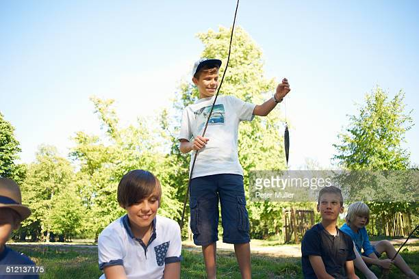 Boy holding fishing net with fish