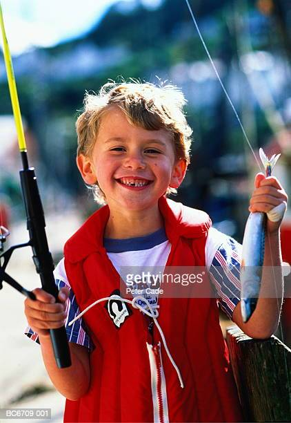 Boy (6-8) holding fishing rod and fish, portrait, outdoors