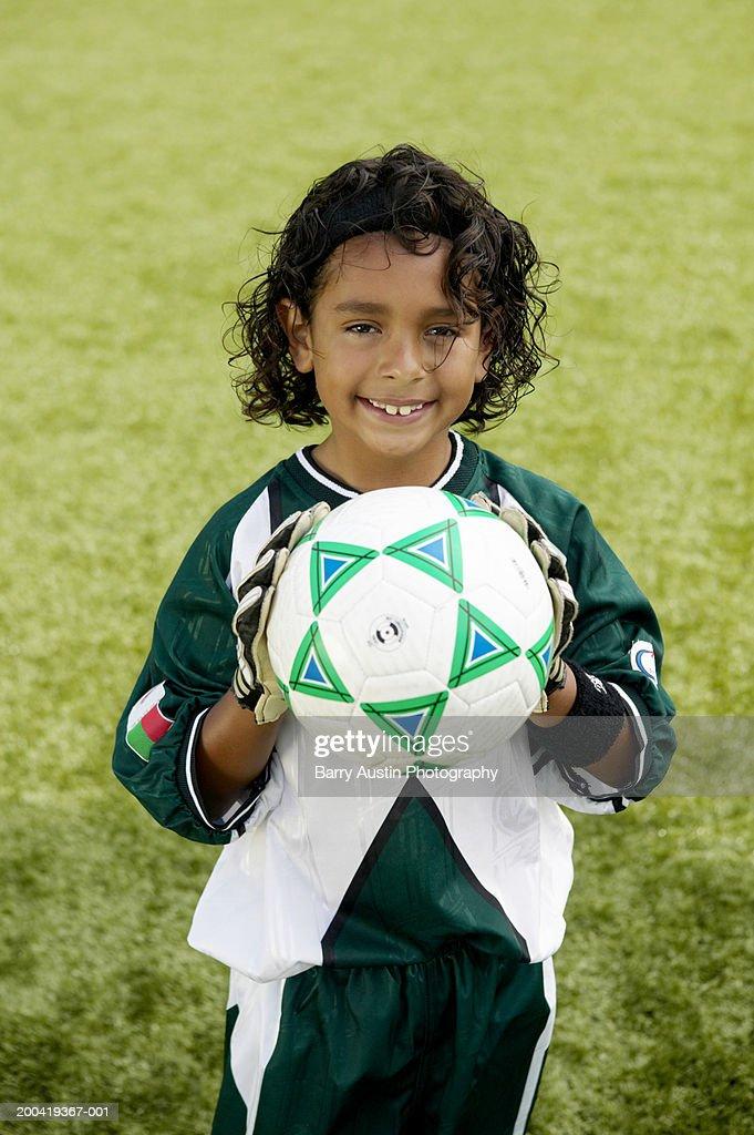 Boy (7-9) holding football, smiling, portrait : Stock Photo