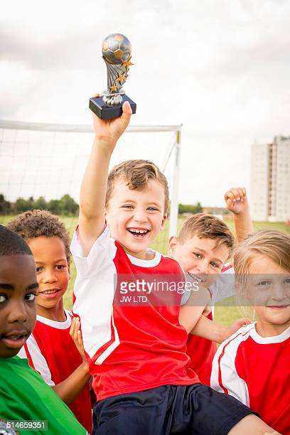 Boy holding football trophy with friends