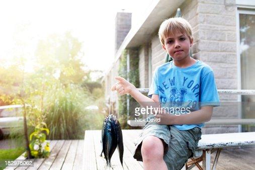 Boy holding freshly caught fish : Stock Photo