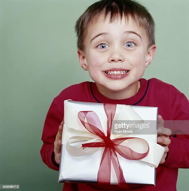 Boy (4-6) holding gift, smiling, portrait