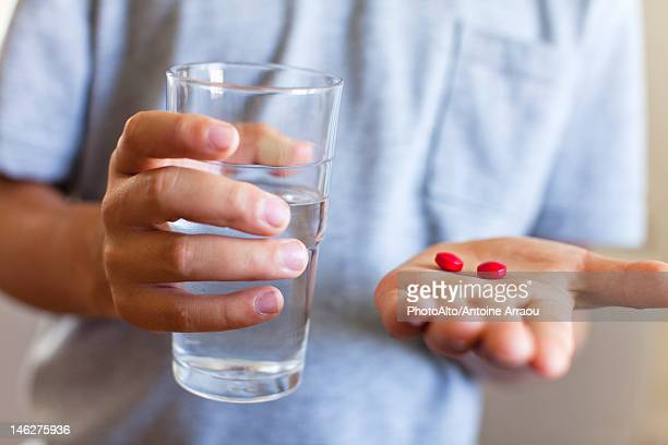 Boy holding glass of water and tablets, cropped