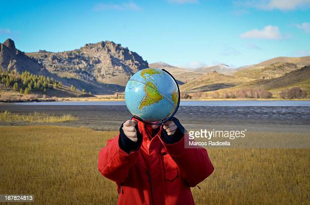 Boy holding globe in patagonian steppe