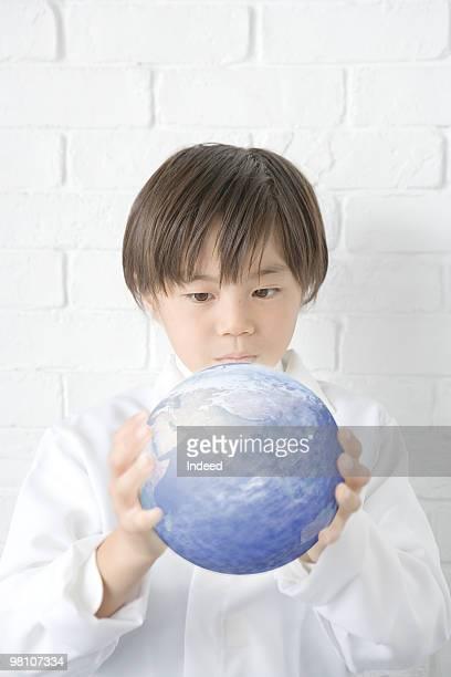 Boy (8-9) holding globe