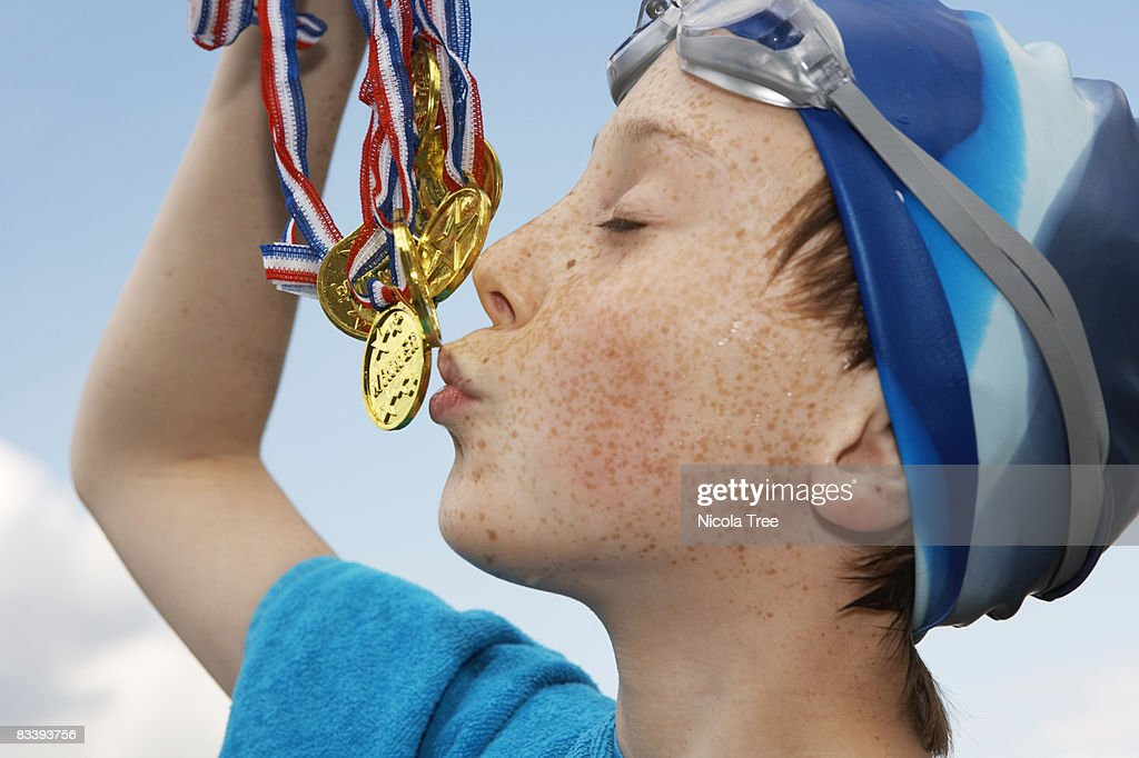 Boy holding gold medals : Stock Photo
