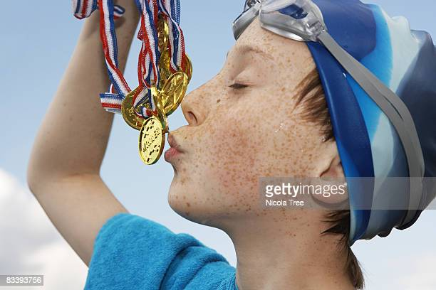 Boy holding gold medals