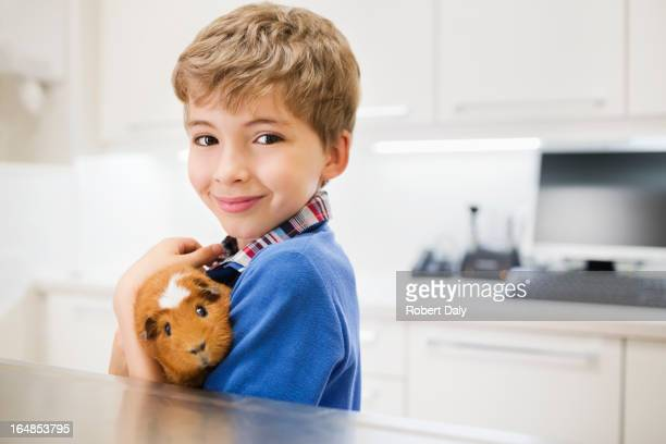 Boy holding guinea pig in vet's surgery