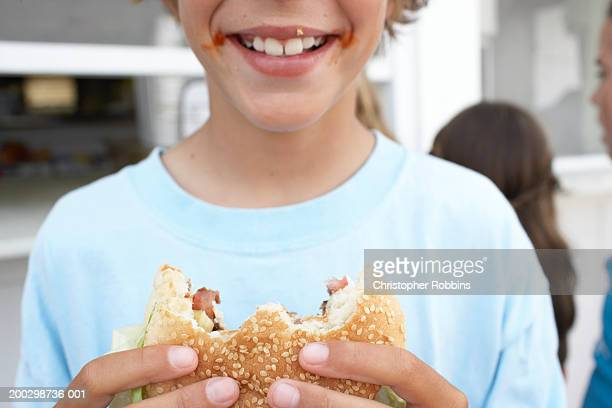 Boy (9-11) holding hamburger with 'bites' missing, smiling, close-up