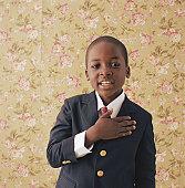 Boy (9-11) holding hand to chest, portrait