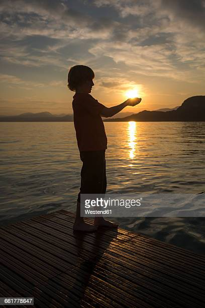 Boy holding hands against the sun at sunset
