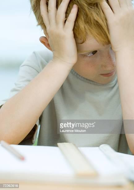 Boy holding head, looking away from homework