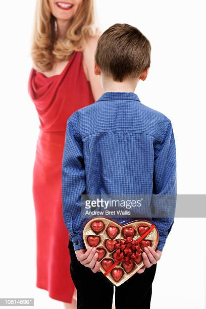 boy holding heart-shaped chocolates behind back