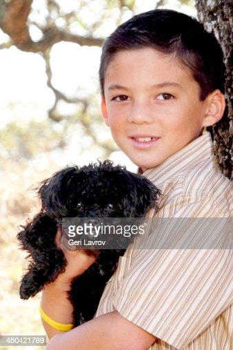 Boy holding his black dog : Stock Photo