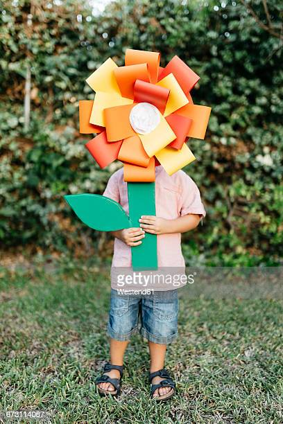 Boy holding home-made cardboard flower in front of his face