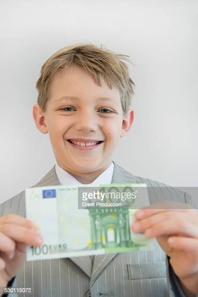 Boy holding hundred Euro in his hand, smiling, portrait