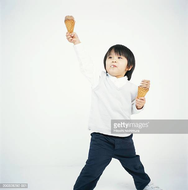 Boy (2-5) holding ice-creams, looking up