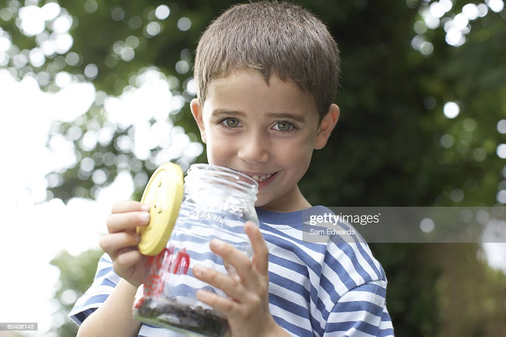 Boy holding insect jar : Stock Photo