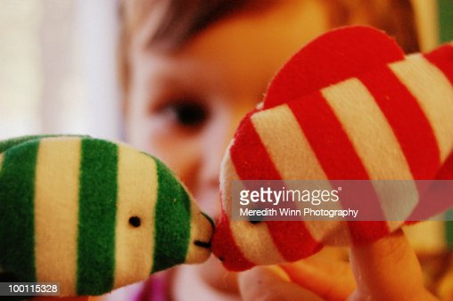 Boy holding kissing fish finger puppets : Stock Photo