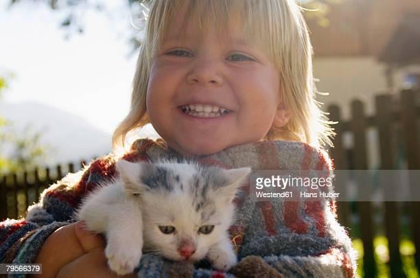 'Boy holding kitten, portrait'