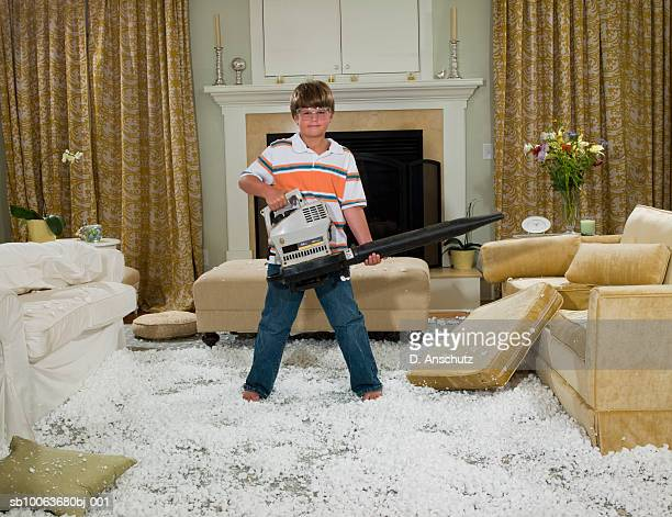 Boy (10-11) holding leaf blower standing in pile of packing peanut in living room, portrait