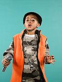 Boy (4-6) holding microphone