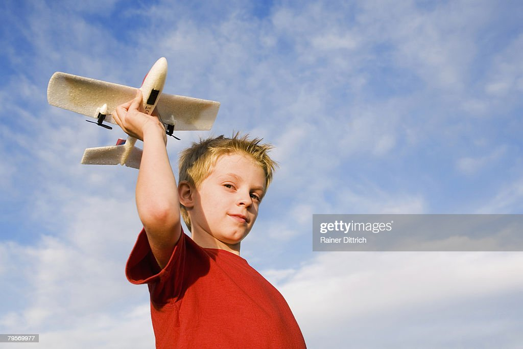 'Boy (10-12) holding model aircraft, low angle view' : Stock Photo