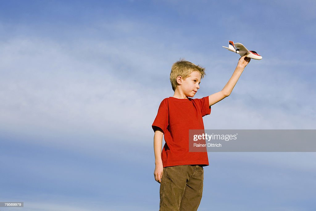 'Boy (10-12) holding model aircraft, side view' : Stock Photo