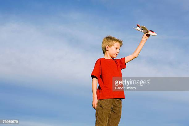 'Boy (10-12) holding model aircraft, side view'