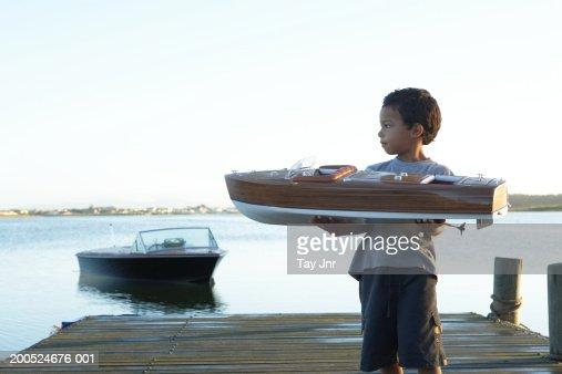 Boy (5-7) holding model boat on jetty : Stock Photo