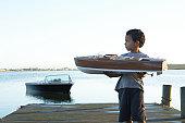 Boy (5-7) holding model boat on jetty