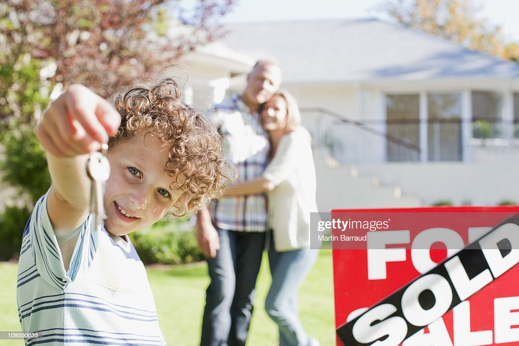 Boy holding new house keys next to sold sign : Stock Photo