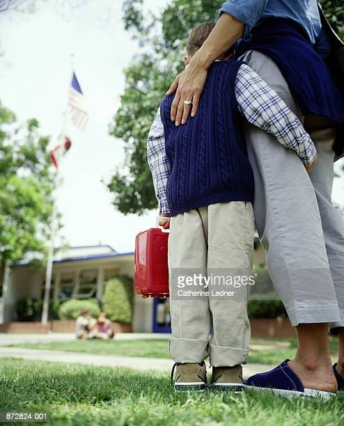 Boy (5-7) holding onto mother's leg in front of school