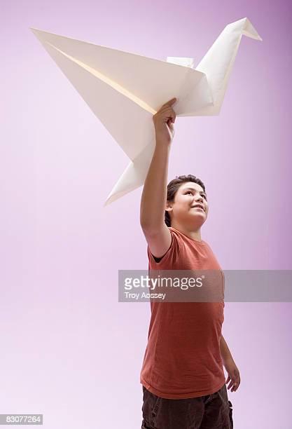 Boy holding origami bird overhead