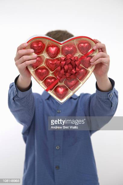 boy holding out a box of heart shaped chocolates