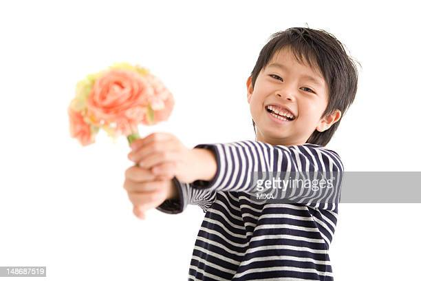 Boy holding out bunch of flower