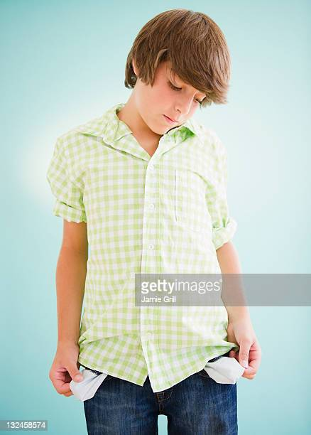 Boy holding out empty pockets, disappointed